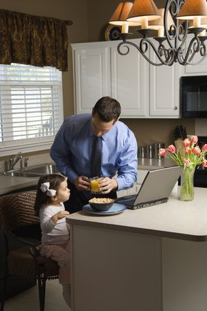 Caucasian father in suit using laptop computer with daughter eating breakfast in kitchen. Stock Photo - 2555161