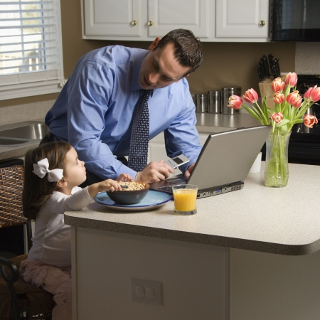 multitasking: Caucasian father in suit using laptop computer with daughter eating breakfast in kitchen.