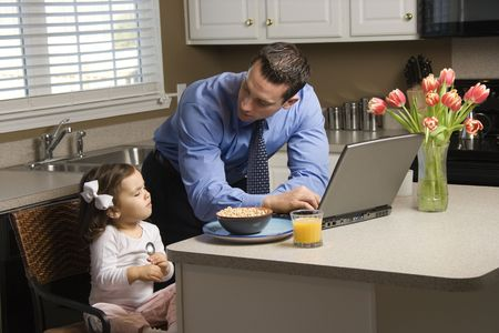 Caucasian father in suit using laptop computer with daughter eating breakfast in kitchen. photo