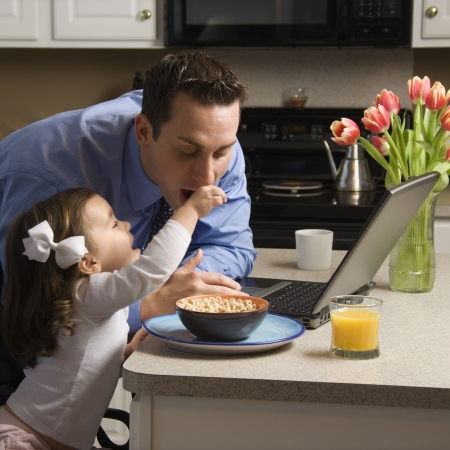 Caucasian father in suit using laptop computer with daughter feeding him breakfast in kitchen. Stock Photo - 2555120