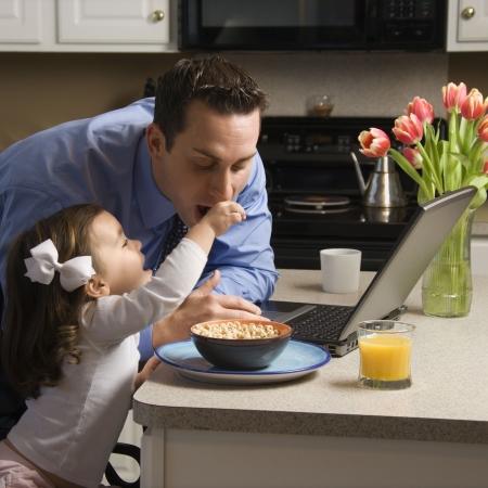 padre e hija: Padre cauc�sico en juego usando la computadora de computadora port�til con la hija que le alimenta el desayuno en cocina.