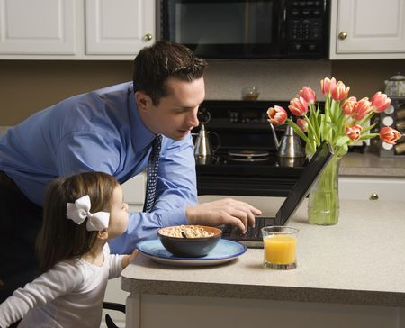 Caucasian father in suit using laptop computer with daughter eating breakfast in kitchen. Stock Photo - 2555132