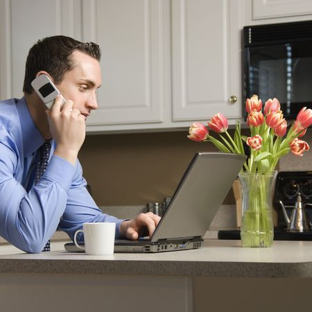 Caucasian man in suit using laptop computer and talking on cellphone in kitchen. Stock Photo - 2555101