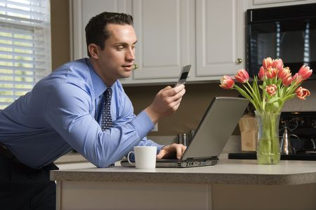 Caucasian man in suit using laptop computer and cellphone in kitchen. Stock Photo - 2555111