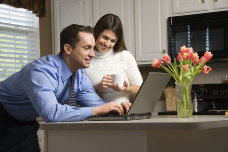 Caucasian couple in kitchen with coffee looking at laptop computer. Stock Photo - 2555099
