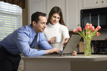 paying: Caucasian couple in kitchen with coffee looking at laptop computer.