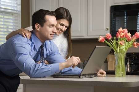 Caucasian couple in kitchen with coffee looking at laptop computer. photo