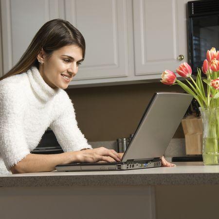 sadece kadınlar: Caucasian woman in kitchen looking at laptop computer.