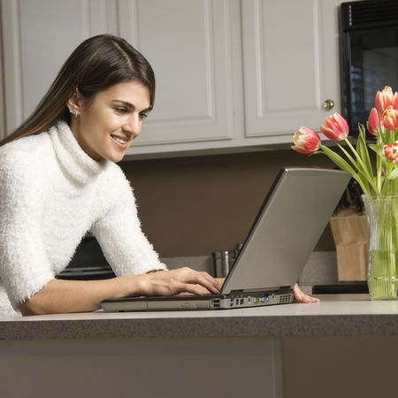 woman work: Caucasian woman in kitchen looking at laptop computer.