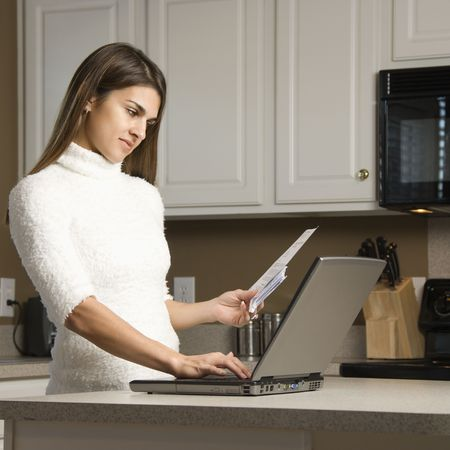 Caucasian woman in kitchen looking at laptop computer. Stock Photo - 2555081