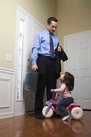 Caucasian businessman   at door with briefcase with daughter looking up at him. photo