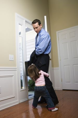 Caucasian businessman   at open door with briefcase with daughter tugging on his leg. photo
