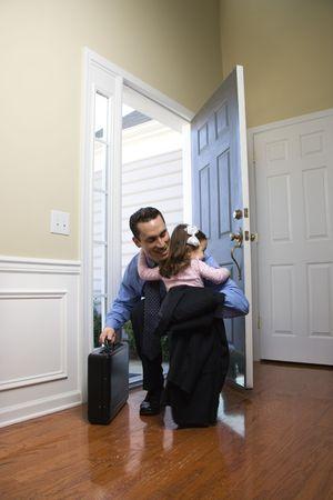 doorways: Caucasian businessman   at open door with briefcase hugging daughter.