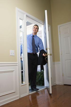 doorway: Caucasian businessman   at open door with briefcase.