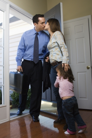 Caucasian businessman   at open door kissing wife while daughter hugs her leg. photo