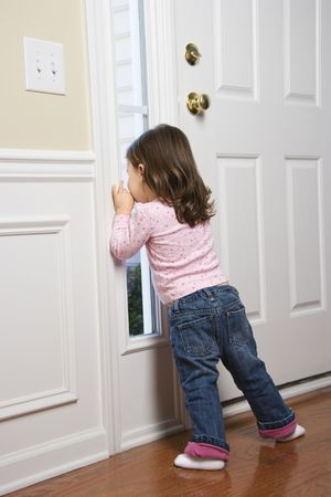 Caucasian girl toddler peeking out of window by door. photo