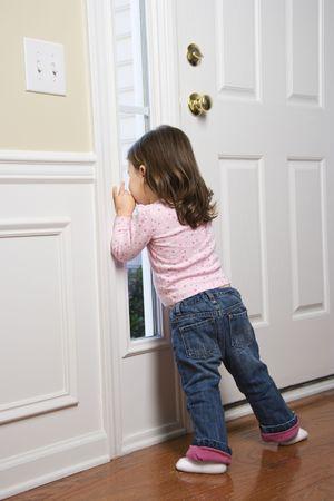 out door: Caucasian girl toddler peeking out of window by door.