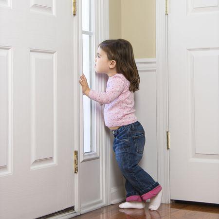 anticipating: Caucasian girl toddler peeking out of window by door.