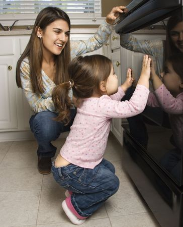 anticipating: Caucasian mother and daughter kneeling by oven peering in.