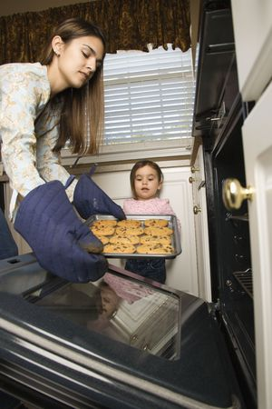 Caucasian mother and daughter  taking cookies out of oven. photo