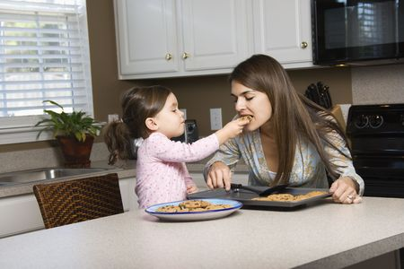 Caucasian girl feeding mother cookies. photo