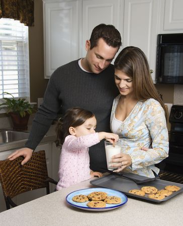 Caucasian mother and father with daughter eating cookies and milk. photo