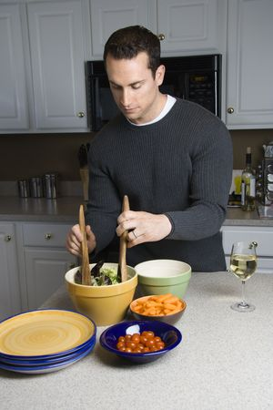 domestic kitchen: Caucasian man making salad on kitchen counter. Stock Photo