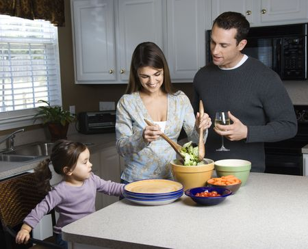 Caucasian woman making salad on kitchen counter with daughter and husband. photo