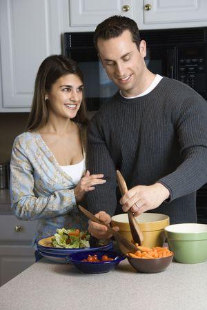 Caucasian couple making salad at kitchen counter. photo
