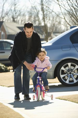 tricycle: Caucasian father helping daughter ride bicycle.