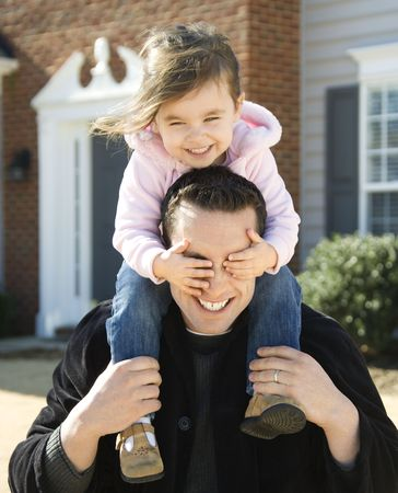 Caucasian father carrying daughter on shoulders. photo