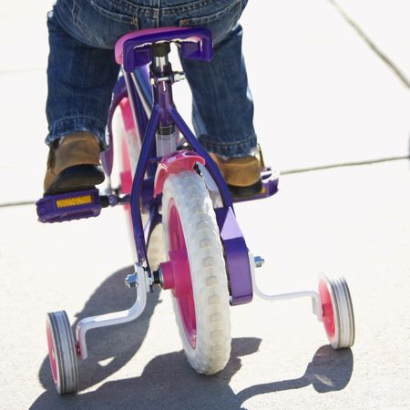 training wheels: Back view of girl riding bicycle with training wheels.