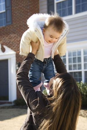 Caucasian mother holding up baby girl in front of house outside. photo
