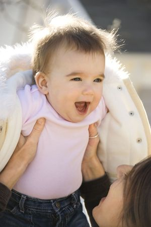 Caucasian mother holding up smiling baby girl. photo