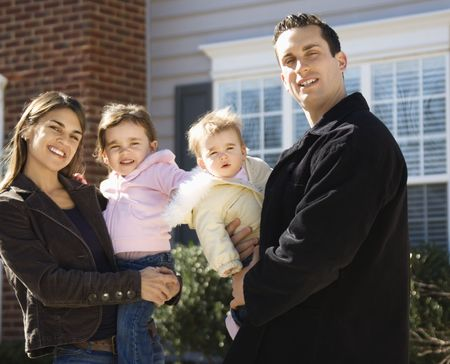 Caucasian mother and father with children standing in front of house. photo