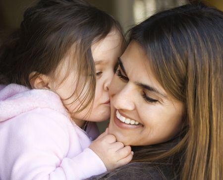 familia abrazo: Cauc�sicos madre de su hija besando la mejilla y sonr�e.