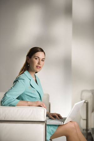 Businesswoman sitting working on laptop computer and looking at viewer. Stock Photo - 2555413
