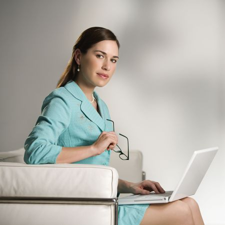 Businesswoman sitting working on laptop computer and looking at viewer. photo