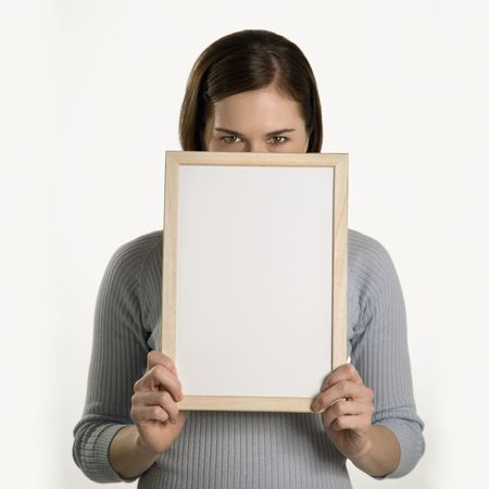 dry erase: Caucasian mid adult professional business woman peeking over top of blank dry erase board in front of her face.