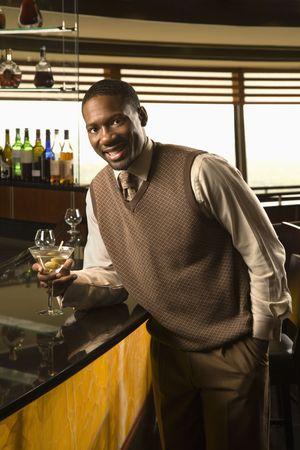 mid adult man: African American mediados hombre adulto se apoya en la barra de martini con mirar espectador.