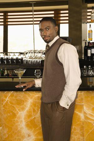 mid adult man: African American mediados hombre adulto de pie en la barra de martini con mirar espectador.