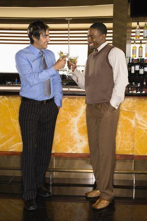 socializando: Dos hombres adultos mediados tostado en la barra de martinis.