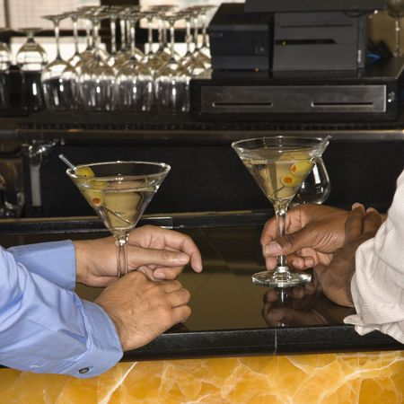 Male hands holding martinis at bar. Stock Photo - 2555197