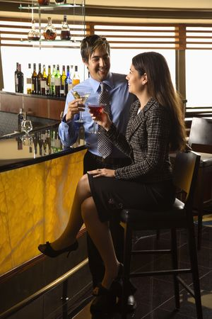 Mid adult Hispanic couple toasting at bar. Stock Photo - 2555192