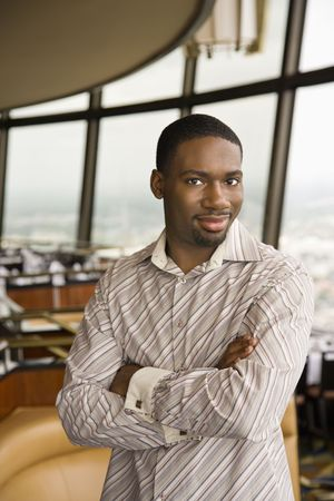 mid adult man: African American mediados de adultos hombre sonriente en espectador con los brazos cruzados.  Foto de archivo