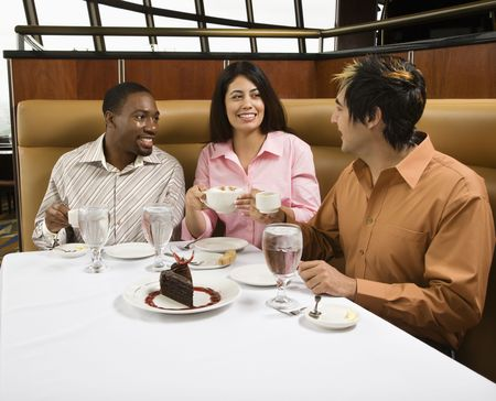 Small group of mid adult friends at restaurant talking and having dessert. photo