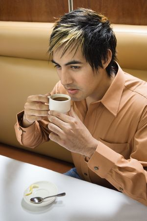 Hispanic mid adult man drinking expresso. photo