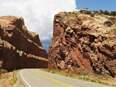 large formation: Rural road dug through large rock formation in Utah. Stock Photo