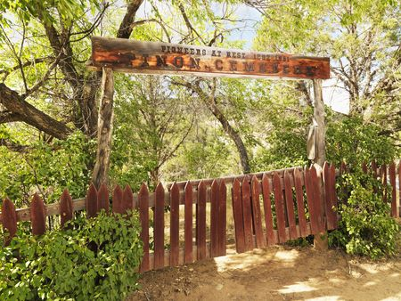 pioneer: Pioneer cemetery entrance with gate and sign in woods.