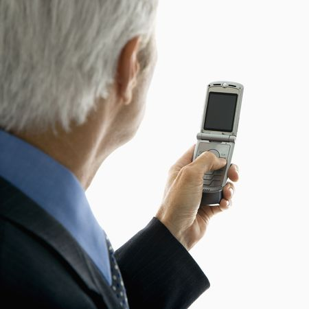 Back view of Caucasian middle aged man looking at cell phone. photo